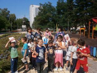 Дечица четат книжки на открито